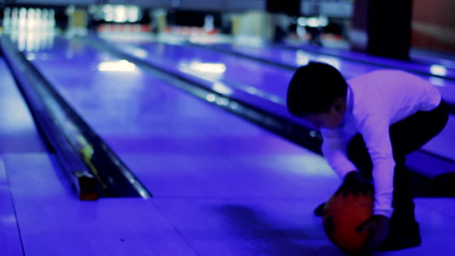 Little boy try to play a game of bowling video
