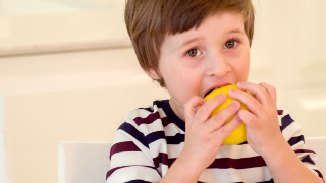 Little boy trying to bite lemon video