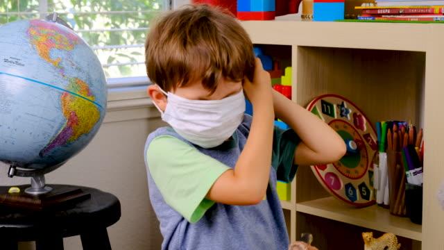 liten pojke försöker sätta in på en skyddande ansiktsmask - förskoleelev bildbanksvideor och videomaterial från bakom kulisserna