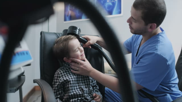 Little Boy Undergoing Transcranial Magnetic Stimulation In Hospital Health Clinic Doctor performing TMS exam to child in hospital lab. Paediatrician doing brain therapy by trans cranial magnetic stimulation on boy in clinic. Health care worker using equipment on ill young people autism stock videos & royalty-free footage