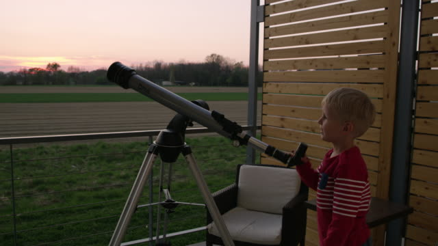 DS Little boy using a telescope Dolly medium shot of a little boy using a telescope for watching stars from the balcony of a house in the countryside. Slovenia. eternity stock videos & royalty-free footage