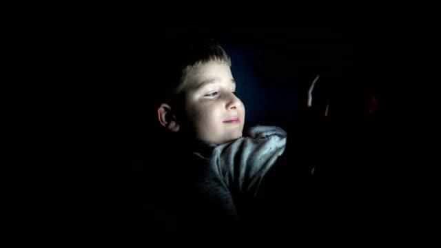 küçük çocuk yatakta dijital tablet kullanma - dijital yerli stok videoları ve detay görüntü çekimi
