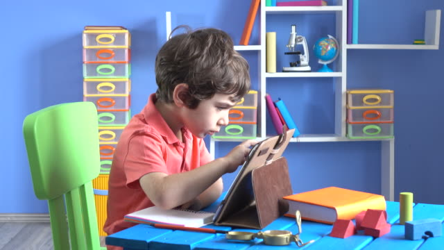 Little Boy Using Digital Tablet In His Room video