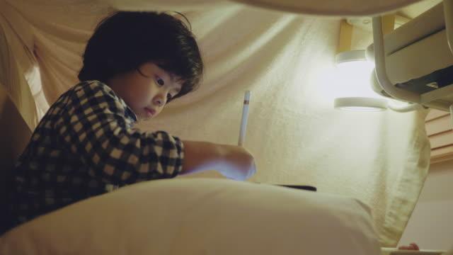 liten pojke som använder digital surfplatta i litet tält hemma - digital reading child bildbanksvideor och videomaterial från bakom kulisserna