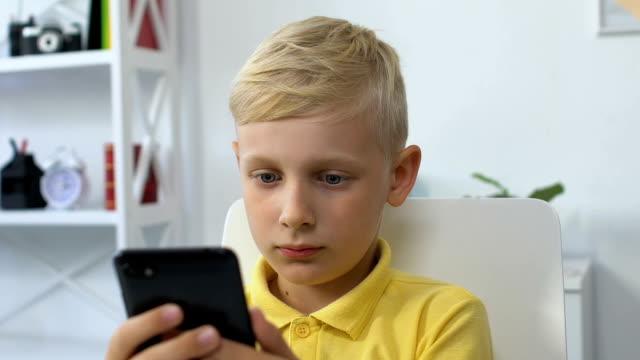 stockvideo's en b-roll-footage met kleine jongen met smartphone thuis, gadget verslaving, technologie invloed - kids online abuse