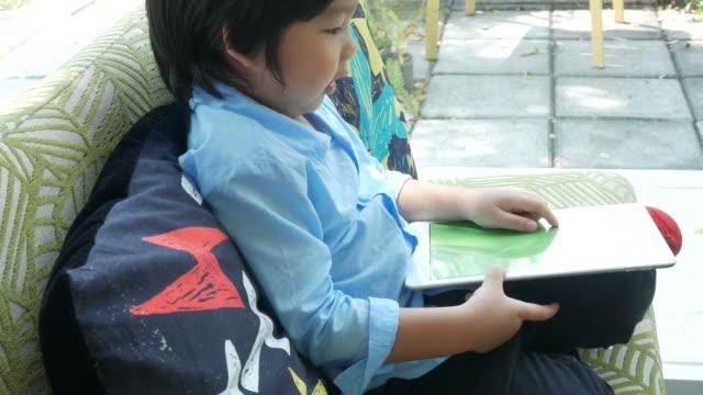 little boy using tablet on sofa
