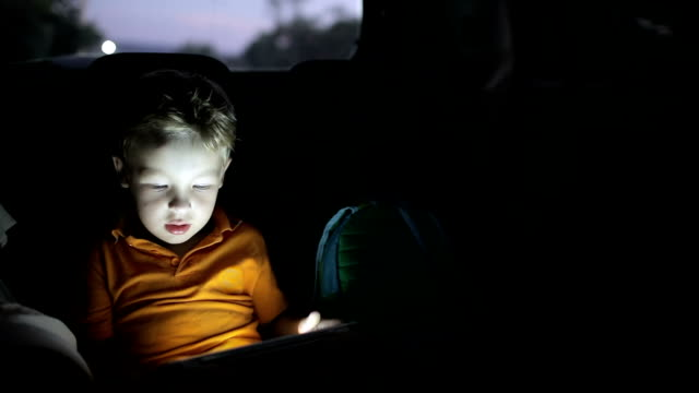 Little boy using tablet pc during car travel at night video