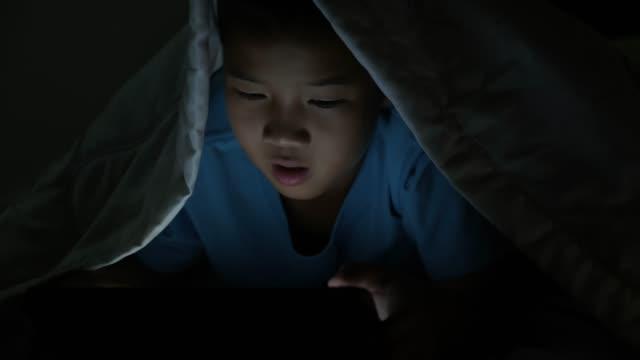 liten pojke som använder tablett under filt på natten i sängen. - digital reading child bildbanksvideor och videomaterial från bakom kulisserna