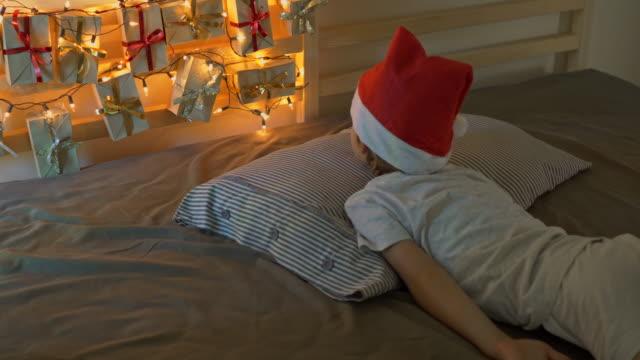 vidéos et rushes de le petit garçon se réveille et voit un calendrier d'avent accroché à un lit s'éclaircir avec des lumières de noel. se préparer pour le concept de noel et du nouvel an. concept de calendrier de l'avent - calendrier de l'avent