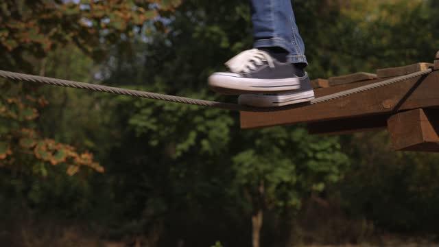vidéos et rushes de un petit garçon marchant sur une corde raide dans un parc de corde, plan rapproché de ses pieds. - danger