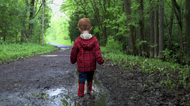 Video Little Boy Walkling in Water Puddle on Campground