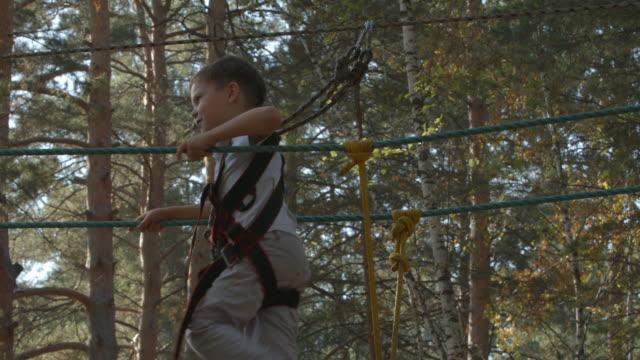 Little boy walks on a rope bridge in an adventure park video
