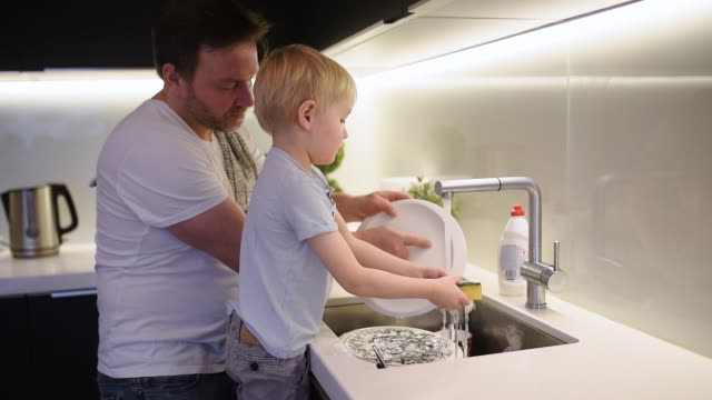little boy washing dirty dishes. child cleans crockery while doing cleaning at home. - lavandino video stock e b–roll