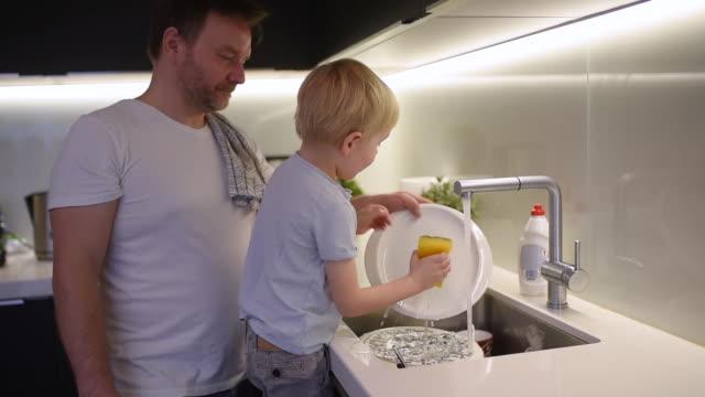 liten pojke tvätta smutsiga rätter. child rengör porslin medan du gör städning hemma. - förskoleelev bildbanksvideor och videomaterial från bakom kulisserna