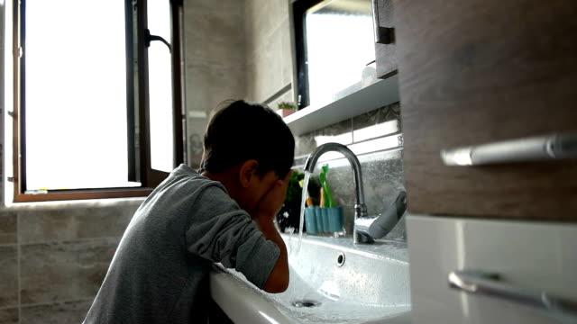 Little boy washing face