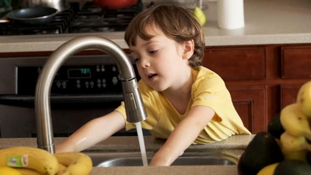 Little boy washing his hands at a kitchen sink Caucasian Little boy washing his hands at a kitchen sink kitchen sink stock videos & royalty-free footage