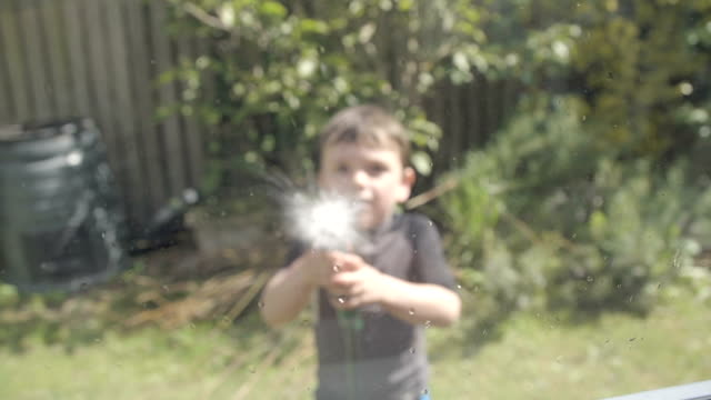piccolo ragazzo lavare le finestre a rallentatore - tubo flessibile video stock e b–roll