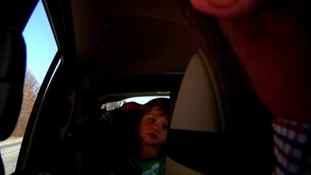 vídeos de stock e filmes b-roll de rapaz assistir filme em aluguer de carros - tv e familia e ecrã
