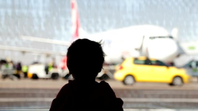 stockvideo's en b-roll-footage met little boy watching planes at the airport - raam bezoek