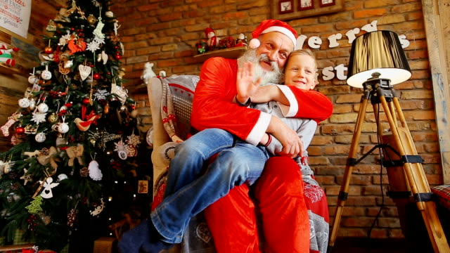 Little boy waves hand and takes pictures with Santa video