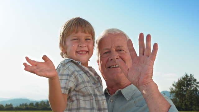 SLO MO Little boy waving into the camera while being held by his grandfather video