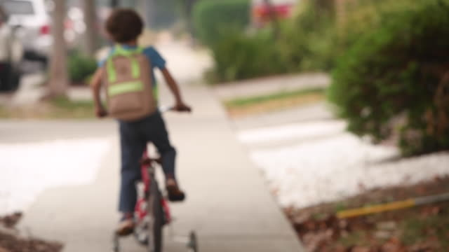 little boy wearing a protective face mask going back to school riding his bicycle carrying a backpack - scolaro video stock e b–roll