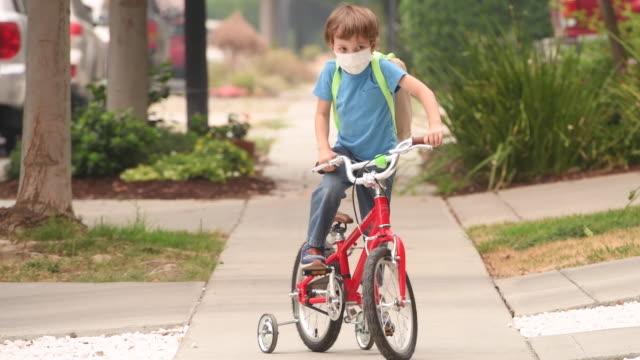stockvideo's en b-roll-footage met weinig jongen die een beschermend gezichtsmasker draagt dat terug naar school gaat die zijn fiets berijdt die een rugzak draagt - schooljongen