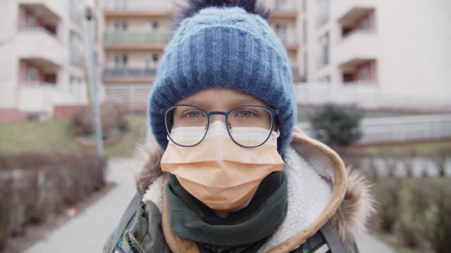 vidéos et rushes de petit garçon utilisant le masque antivirus allant à l'école - enfant masque