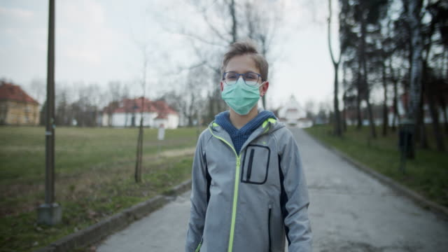 vidéos et rushes de le petit garçon utilisant le masque d'anti-virus marche dans le stationnement - enfant masque