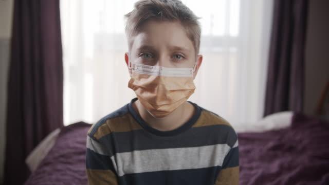 vidéos et rushes de petit garçon utilisant le masque d'anti-virus restant à la maison - enfant masque