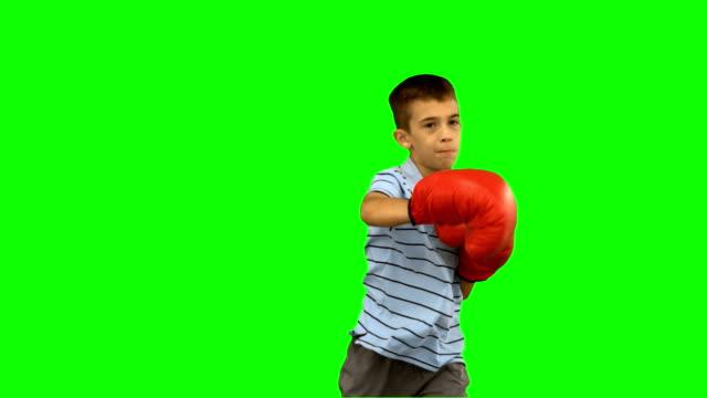 ragazzino con guantoni da boxe pugilato - colpire con un pugno video stock e b–roll