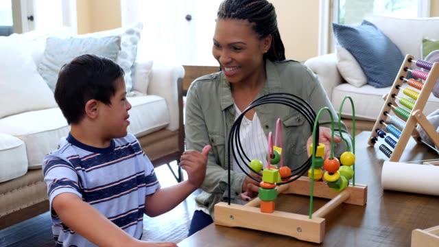 liten pojke med besegra syndromet leker med den kvinnliga handledaren - fysiskt funktionshinder bildbanksvideor och videomaterial från bakom kulisserna