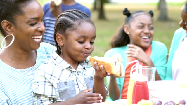 Little boy with family, eating hotdog at cookout A cute little 3 year old African-American boy sitting in mother's lap eating a hotdog, with family at a backyard cookout. hot dog stock videos & royalty-free footage