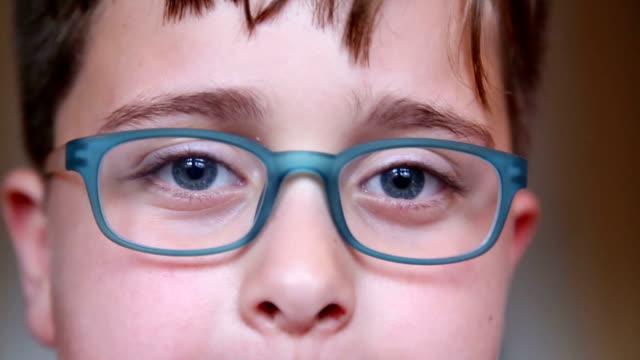 kleiner junge mit brille, nahaufnahme - brille stock-videos und b-roll-filmmaterial
