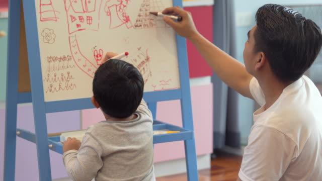 vídeos de stock, filmes e b-roll de rapaz pequeno com seu pai que desenha na placa branca em casa-sustentação e crianças da família - salas de aula
