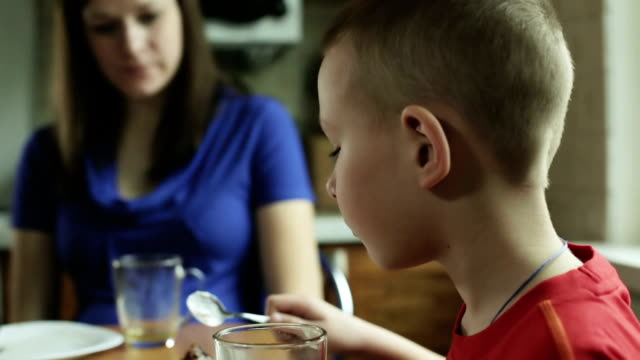 Little boy with short hair is eating cake and drinking tea. video