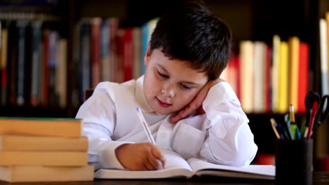 little boy writing and thinking video