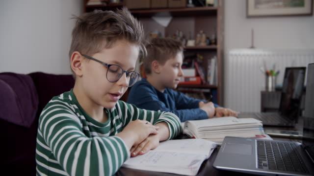 Video Little boys attending to online school class.