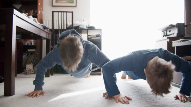 Little boys doing push-ups at home