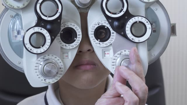 der kleine junge sieht augenuntersuchung beim augenarzt aus der nähe. - augenoptiker stock-videos und b-roll-filmmaterial