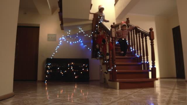 stockvideo's en b-roll-footage met jongetjes in santa hoeden. - christmas tree