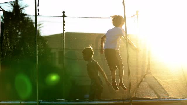 vídeos y material grabado en eventos de stock de niños pequeños saltando dentro del trampolín al aire libre - backyard