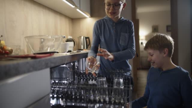 食事の後に食器洗い機を積む小さな男の子 - 兄弟姉妹点の映像素材/bロール