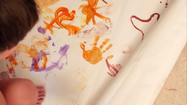 stockvideo's en b-roll-footage met jongetjes schilderen met hun handpalmen op papier - background baby