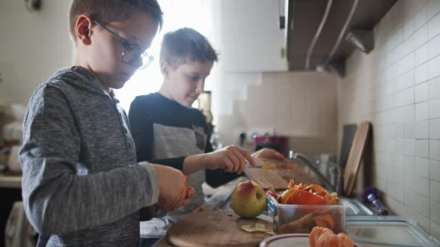 kleine jungen schälen obst in der küche und sammeln organische abfälle - geschält stock-videos und b-roll-filmmaterial