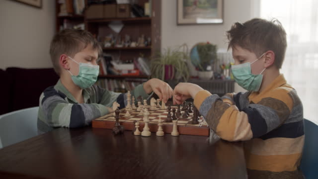vidéos et rushes de petits garçons jouant aux échecs ensemble pendant une épidémie de virus - enfant masque