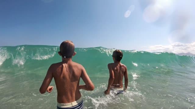 Little boys splashed by sea wave