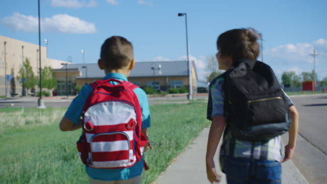 Little Boys Walk to School A Caucasian elementary-aged boy catches up to his friend as they both walk to school under a blue sky. elementary age stock videos & royalty-free footage