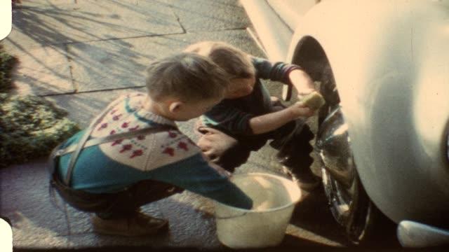 Little boys washing daddy's car (vintage 8mm film)