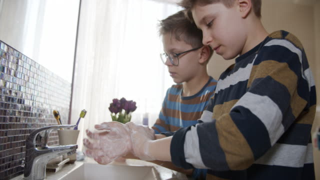 Little boys washing hands thoroughly
